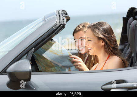 Two tourists reading a map searching destination in a convertible car on summer vacation - Stock Photo