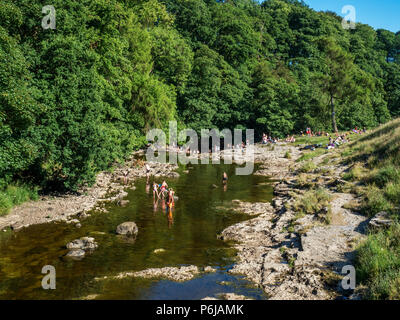 Ribblesdale, UK, 30 June 2018. Crowds paddling in the River Ribble at Stainforth Force waterfall near the village of Stainforth in Ribblesdale, Yorkshire Dales National Park during the summer heatwave Credit: Mark Sunderland/Alamy Live News - Stock Photo