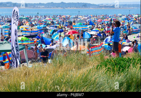 West Wittering beach   on a hot summers weekend in july ,packed with day trippers enjoying the heatwave and swimming in the sparkling water on its Blue Flag beach - Stock Photo