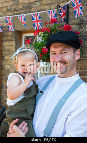 Kidderminster, UK. 30th June, 2018. A journey back in time begins on the Severn Valley Railway as we turn the clock back to the 1940s. Visitors and staff pull out all the stops to ensure a realistic wartime Britain is experienced on this heritage railway line. A happy father poses here at a vintage station for a portrait photograph with his cute little baby girl in his arms - both dressed in 1940s costume. Credit: Lee Hudson/Alamy Live News - Stock Photo