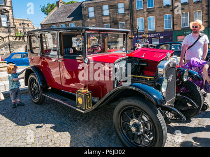 The Cross, Kirkgate, Linlithgow, West Lothian, Scotland, United Kingdom, 30th June 2018. Enthusiasts display sparkling vintage cars  at a rally  on a sunny Summer day. A classic pre-war Austin Windsor Saloon with a small boy looking at the wheel and a man in a Panama hat admiring it - Stock Photo