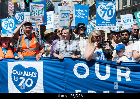 London, UK. 30th June, 2018. Shadow Health Secretary Jonathan Ashworth (C) joined thousands of demonstrators taking part in a march followed by a rally outside Downing Street in central London to celebrate the 70th anniversary of the National Health Service. Protesters call for an end to austerity policies which lead to underfunding and staff shortages in the NHS, and demand that it remains publicly owned and accessible to everyone. Credit: Wiktor Szymanowicz/Alamy Live News - Stock Photo