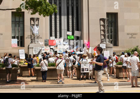 Washington DC, USA. 30th Jun, 2018. People attach protest signs to the doors of the Department of Justice during the Families Belong Together Rally in Washington, D.C., June 30, 2018.. Credit: Robert Meyers/Alamy Live News - Stock Photo