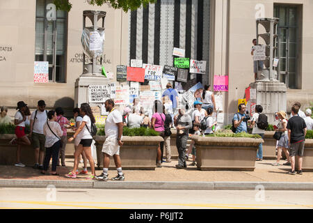 Washington DC, USA. 30th Jun, 2018. People attach protest signs to the doors of the Department of Justice during the Families Belong Together Rally in Washington, D.C., June 30, 2018. Credit: Robert Meyers/Alamy Live News - Stock Photo