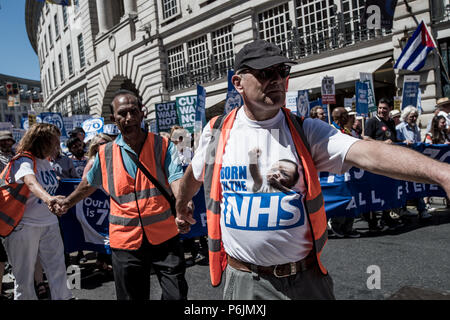 Members of the march organization holding hands. Tens of thousands of people marched during the hot Saturday weather through London to celebrate and demonstrate over Britain's National Health Service (NHS), ahead of its 70th birthday next week. - Stock Photo