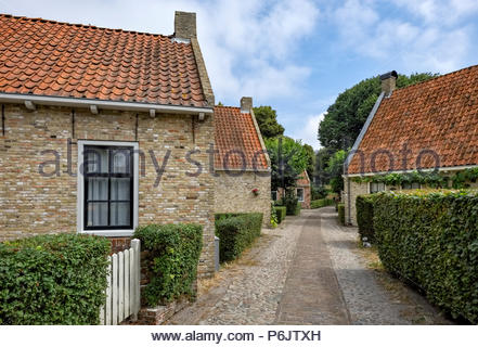 A cobblestone path runs between brick houses in the village at Vesting Bourtange, the star-shaped fortress in Groningen Province, The Netherlands. - Stock Photo