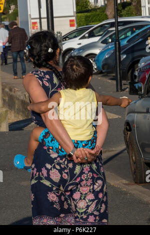 woman carrying baby on her back, piggy back. - Stock Photo