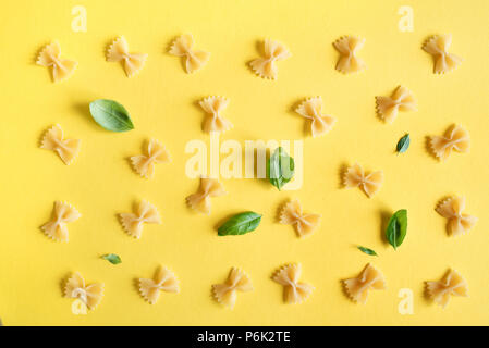 Farfalle Pasta on yellow background, top view, flat lay. Pattern uncooked farfalle pasta with basil leaves. - Stock Photo