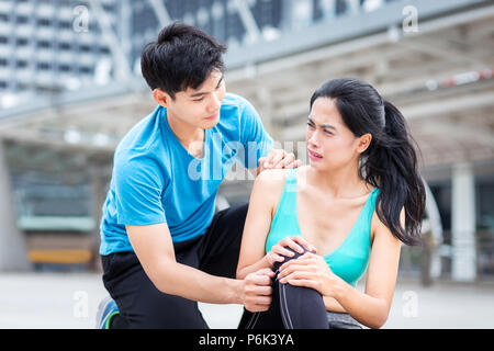 running injury, man help sport girl from  ankle hurt accident from playing sport in the city - Stock Photo