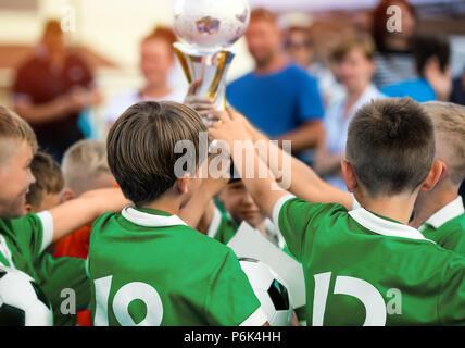 Kids Raising Golden Cup for Winning Sports Team. Children in Green Sportswear Celebrating Sport Success. Happy Kids Celebrate the Victory - Stock Photo