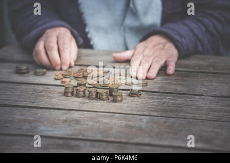 Money, coins, the grandmother on pension and the concept of life, minimum - wrinkled hands of the old woman touch coins on a wooden table - Stock Photo
