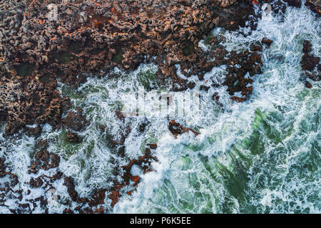 Aerial view of rocky coastline with crashing waves. - Stock Photo