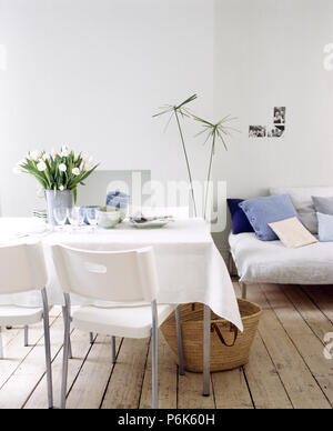 Crisp white linen cloth and a vase of white tulips on a table with white plastic chairs in an urban dining room with wooden flooring - Stock Photo