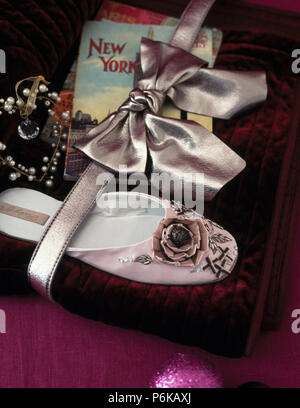 Close-up of rose encrusted silk slipper and vintage book tied with metallic silver leather bow - Stock Photo