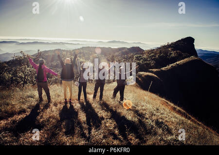 Group of Traveler on mountain summit enjoying aerial view hands raised over clouds Travel Lifestyle success concept adventure active vacations outdoor - Stock Photo