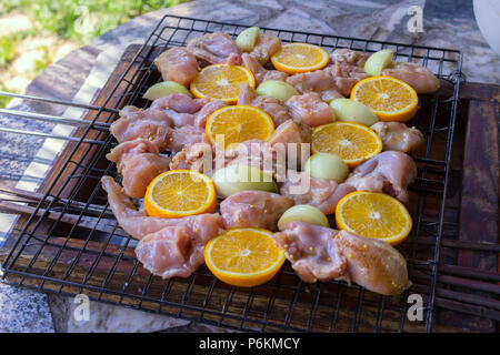 Process of cooking raw spicy chicken with orange - Stock Photo