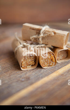 Homemade muesli bars with nuts and dried fruits on a wooden board - Stock Photo