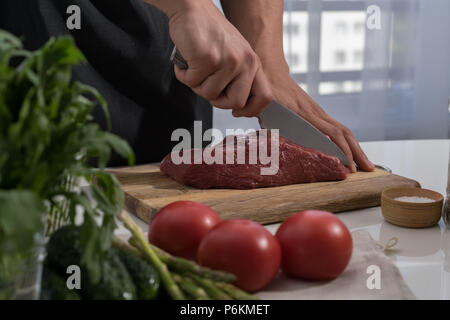 Butcher cutting beef in the kitchen - Stock Photo
