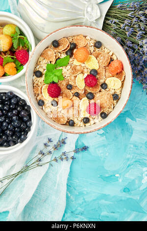 Healthy vegetarian breakfast. Oatmeal, granola with raspberries and blueberry in bowl over blue background, Bouquet lavender. Top view. Flat lay. - Stock Photo