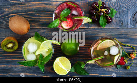 Summer cold drinks with fresh fruits, berries and mint. Strawberry mojito, cherry smoothies, cocktail of kiwi in glasses on a wooden table. Drinks at  - Stock Photo