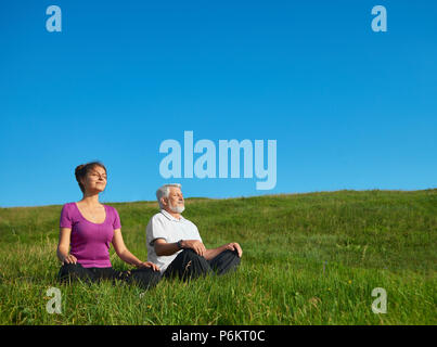 Young girl and old man meditating sitting in the field. Sitting in lotus pose on bright saturated sky background. Looking positive, satisfied, feeling good, concentrated. Calm and silent. - Stock Photo