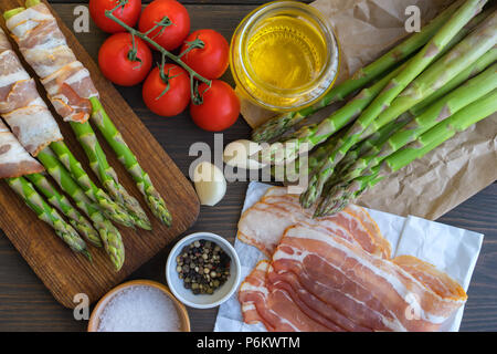 Fresh organic asparagus wrapped in Parma ham on a cutting board - Stock Photo