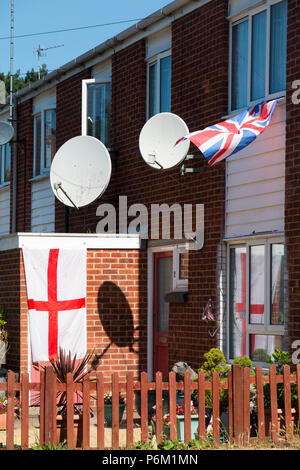 A residential house which is fitted with satellite receiver dishes and decked out with English St George flag and British Union Jack flags. England. UK. (99) - Stock Photo