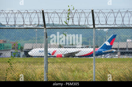 Phuket, Thailand - Apr 23, 2018. Fence with barbed wire around airport with a docking airplane in Phuket International Airport (HKT). - Stock Photo