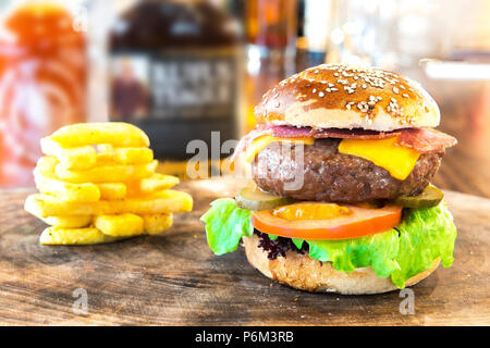 Hamburger. Close-up fresh delicious tasty homemade burger. This hamburger with french fries on wooden table - Stock Photo