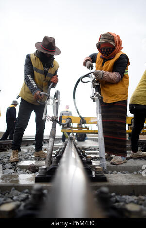 Golmud, China's Qinghai Province. 30th June, 2018. Workers reinforce tracks near the Tanggula Station of the Qinghai-Tibet railway, northwest China's Qinghai Province, June 30, 2018. Maintenance workers stick to their posts everyday to guarantee the operation of the Qinghai-Tibet railway at the Tanggula Station with an altitude of 5,072 meters above sea level. The 1,956-kilometer-long railway, which began service in July 2006, is the world's highest plateau railroad connecting Xining in Qinghai and Lhasa in Tibet Autonomous Region. Credit: Zhang Hongxiang/Xinhua/Alamy Live News - Stock Photo