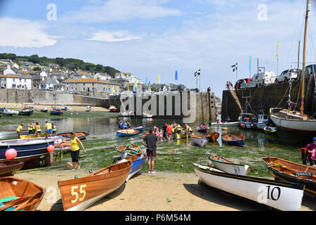 Mousehole, Cornwall, UK. 1st July 2018. UK Weather. After early morning rain the 1st of July brought another hot and humid afternoon to Cornwall. The annual rowing regatta took place, with teams from around Cornwall, and one from Italy taking part in the competition. Credit: Simon Maycock/Alamy Live News - Stock Photo