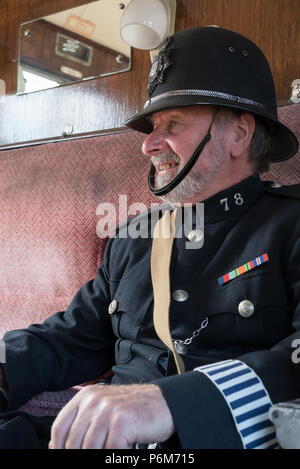 Kidderminster, UK. 1st July, 2018. A journey back in time continues at the Severn Valley Railway as we turn the clock back to the 1940s. Visitors and staff pull out all the stops to ensure a realistic second world war Britain is experienced on this heritage railway line. A vintage policeman, inside vintage railway carriage, sweltering in helmet & full police uniform, ensures a British Bobby is always present. Credit: Lee Hudson/Alamy Live News - Stock Photo