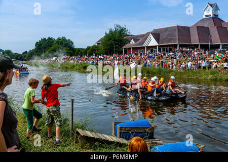 Local children throw eggs and flour bombs at the home made rafts taking part in the annual Ouseday Raft Race held on the River Ouse In Lewes, Sussex, UK - Stock Photo