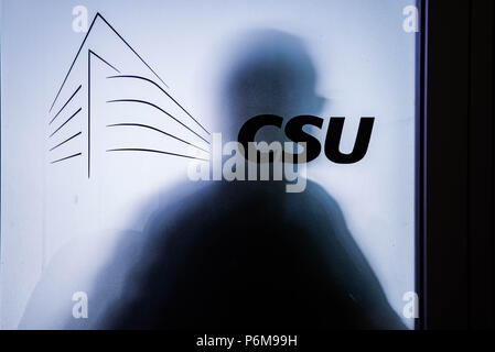 Munich, Bavaria, Germany. 1st July, 2018. Someone stands behind the frosted door of a CSU conference room where meetings are taking place to determine the future of Germany's government. Officials of the Bavarian CSU party hold a meeting to determine if the CSU will split from its union with Angela Merkel's CDU, effectively dissolving Germany's government, or if it will continue. The point of difference is regarding the sending of migrants back to the country of their first registration at the German border. Credit: Sachelle Babbar/ZUMA Wire/Alamy Live News - Stock Photo