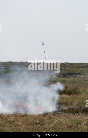 Lancashire, UK. 1 July 2018 - A fire helicopter dumps 1000 litres of water in an attempt to control the growing moorland fire on Winter Hill and Rivington Pike which was started a number of days ago. Fire crews from across the UK have converged on Winter Hill to control the blaze which is growing by metres per hour. Lancashire Fire and Rescue and Lancashire Police are leading the response to the 'major incident'. Credit: Benjamin Wareing/Alamy Live News - Stock Photo