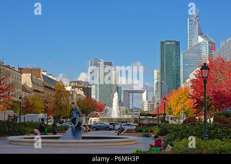 View from a autumn park in Neuilly-sur-Seine on the highrise buildings and Grand Arch monument of La Defense business district behind on a sunny day , - Stock Photo