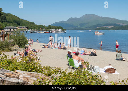 Luss beach, Loch Lomond and Ben Lomond busy on a hot summer day, Scotland, UK - Stock Photo