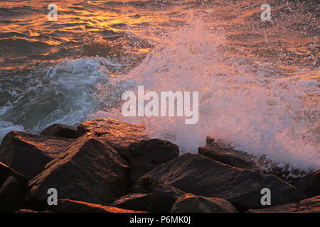 Warnemuende, waves breaking in the evening light on rock - Stock Photo