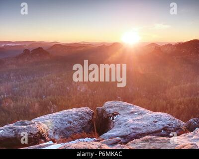 Morning view over sandstone formation into misty valley. Fantastic dreamy sunrise on top of rocky mountain - Stock Photo