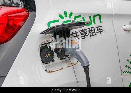 Charging an electric car with the power cable supply plugged from special station on the street in tourist city Yangshuo of China. - Stock Photo