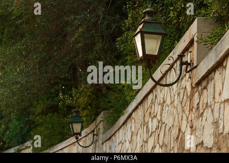 Old stone wall with lantern. street vintage lantern hanging from a rustic stone wall against a background of green leaves. Romantic urban scenery with classical lighting - Stock Photo