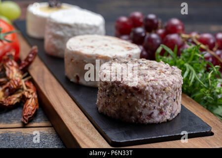 French soft cheeses, variety of different taste goat milk natural cheeses on granite plate close up sesrved as dessert - Stock Photo