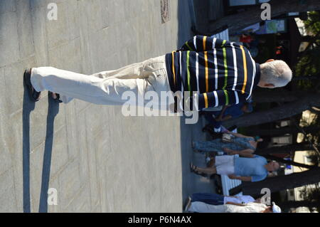 A gray-haired ELDERLY man in white trousers, WALKS IN the PARK on a SUMMER DAY - Stock Photo