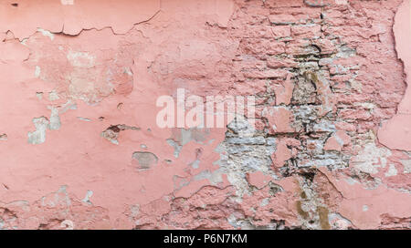 Full frame background of a weathered, damaged and plastered wall painted in pink. Plaster is partly peeled off revealing old bricks. - Stock Photo