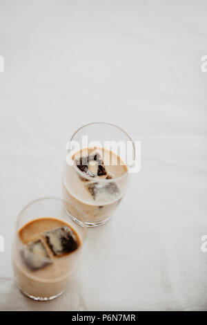 Frozen coffee ice cubes in a glass poured with milk to make a refreshing summer iced coffee drink. White background, isolated, copy space. - Stock Photo