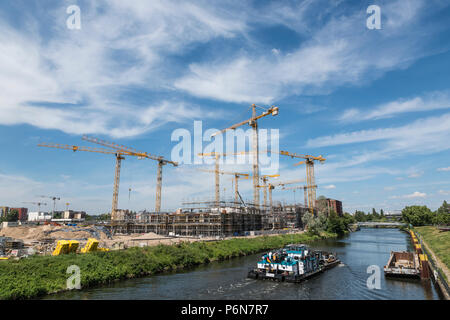 BERLIN, GERMANY, MAY 24, 2018: Many operating cranes at building site in Berlin, beside a canal. - Stock Photo