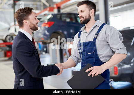 Mechanic Shaking Hands with Businessman - Stock Photo