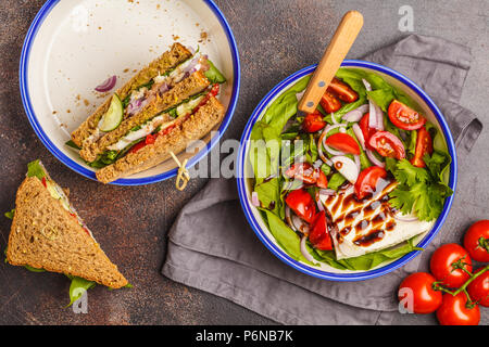 Bright summer salad with tomatoes, onions, balsamic and goat cheese with meat and cheese sandwiches. Food flat lay on dark background. - Stock Photo