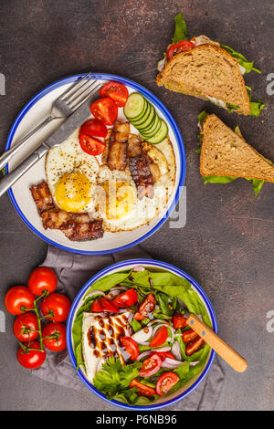Food flat lay: vegetable salad with goat cheese, sandwiches with cheese and vegetables and fried eggs with bacon. Beautiful bright breakfast on a dark - Stock Photo