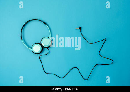 Table top view aerial image of accessories listening radio music background concept.Flat lay headphones on modern rustic blue paper wallpaper.Free spa - Stock Photo